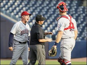 Lehigh Valley IronPigs manager Ryne Sandberg gives an earful to third base umpire Chris Ward as he's about to get ejected while catcher Erik Kratz looks on, during the first inning against the Mud Hens at Fifth Third Field. Sandberg was heated after Ward ejected pitcher Eddie Bonine.
