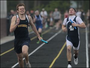 Woodmore's Cody Curry, left, wins the 200 meter relay for his team during SLL track meet at Genoa High School.
