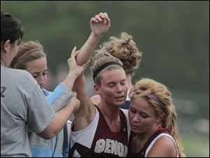 Genoa's Tiffany Wright is helped off the track after winning the 800 meter run during SLL track meet.