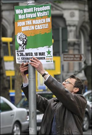 A man puts up a placard to advertise a protest march to coincide with the visit by Britain's Queen Elizabeth II to Ireland.