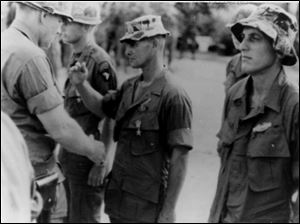 Sgt. William Doyle, center, in soft-brimmed hat, received a medal at Phan Rang in November, 1967. He has admitted killing Vietnamese civilians.