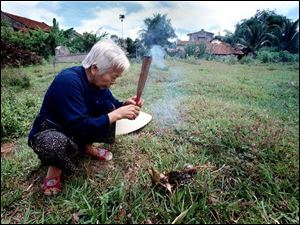 Tam Hau lights incense before kneeling in prayer at the grave of her uncle, Dao Hue, who was killed by a Tig