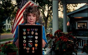 Joyce Wood, with her late husband's medals, says he was 'very disturbed' by his experiences in Vietnam.