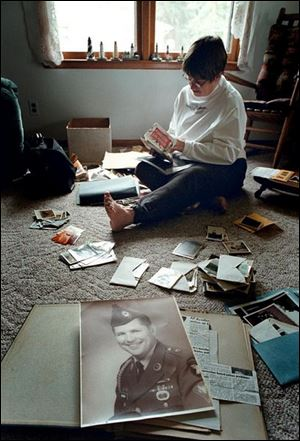 Karen Bruner of Colon, Mich., examines photos of her late husband, who died in 1997.