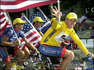 Lance Armstrong, right, rides down the Champs Elysees avenue with his teammates Georges Hincapie, and Tyler Hamilton, left, after he won the Tour de France cycling race in 2001.