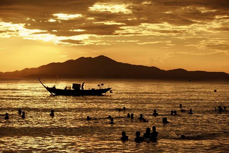 Tourists-swim-in-the-South-China-Sea-near-a-fishing-boat-as-the-sun-rises