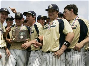 The St. John's baseball team gathers with the trophy after the Titans defeated Whitmer during the district final at Ned Skeldon Stadium.
