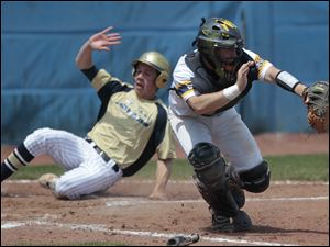 St. John's runner Jesse Adams scores the go-ahead run as Whitmer catcher Scott Pfeiffer catches the ball.