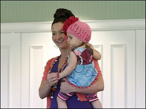 Erica Stearns holds daughter Ava Leigh during the Toledo Opera Guild Fashion Show.