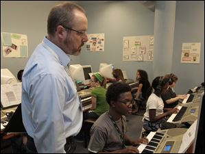 Music teacher Jay Welenc instructs students, including seventh-grader Andrew Nauden, center, in the keyboard lab at the Toledo School for the Arts.