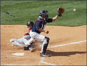 PawSox infielder Lars Anderson tries to slide home as Mud Hens catcher Omir Santos receives the throw while blocking the plate in the ninth inning.