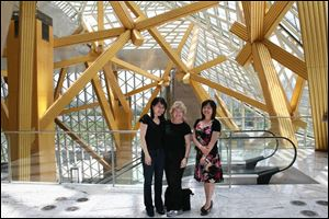 Amy Chang, left, the Toledo Symphony's associate principal cellist, Kathy Carroll, the symphony's president and chief executive, and Xia Xu, the Shenzhen Concert Hall's artistic director, gather inside the four-year-old building.