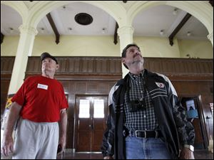 Craig Walter of Toledo, a 1965 graduate of Libbey High School, left, and Bill Albert of Waterville, a 1966 graduate, look around the school's old fourth floor cafeteria, during the auction.