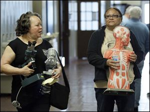 Gladys Green, left, carries microscopes and Letha Goree carries a science mannequin after they were the winning bidders.