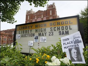Dotted with posters promoting its preservation, the Libbey High School sign announces the auction of the contents of the school.