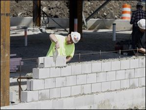 Workers construct part of a block wall on the Stroh Center site, March, 2010.