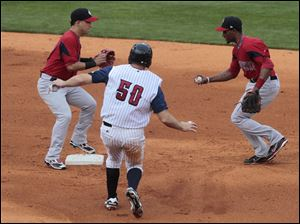 The Mud Hens' Scott Thorman is forced out on this play by Pawtucket's Tony Thomas,  right, who rans across the base for the out.