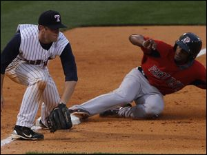 Hens third baseman Danny Worth gets the throw late and Pawtucket's Tony Thomas slides safely into third.