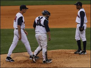 Mud Hens pitching coach A.J. Sager, left, and catcher Omir Santos approach pitcher Jose Ortega during the beginning the 9th inning.