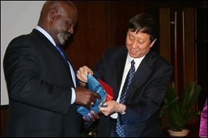 Toledo Mayor Mike Bell receives a gift from Zhu Naizhen, vice mayor of Mudanjiang, during an hours-long meeting to discuss business opportunities. The two promised to visit each other's cities this year.