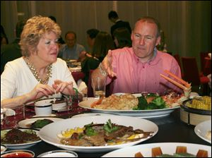 Kathy Carroll, left , director of the Toledo Symphony, and Scott Prephan, a real estate broker who spearheaded some of the initial Toledo-Chinese relations, enjoy a traditional dinner with the delegation after arriving in Shenzhen.
