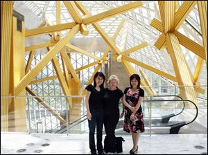 Xia Xu, right, the artistic director of Shenzhen Concert Hall, welcomes the Toledo Symphony cellist Amy Chang, left and director Kathy Carroll.