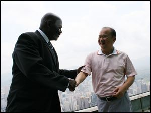 Toledo Mayor Mike Bell, atop the Empire Building in China, shakes hands with Wu King Hung, who with a partner bought The Docks in Toledo.