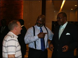 Scott Prephan, left and Toledo Mayor Mike Bell, center, talk in Beijing with John Olago-Aluoch, a cousin of President Barack Obama and a Kenyan Parliament member.