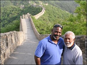Toledo Mayor Mike Bell, left, and his father, Norman, on top of the Great Wall of China. Blade