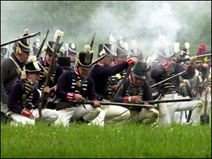 Soldiers reload their muskets during a past re-enactment of the battle at Fort Meigs.