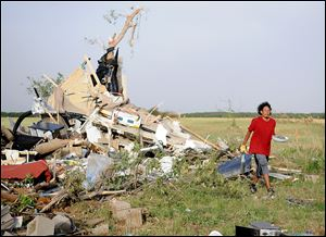 Harley Voyager salvages items from the home of Jeremy and Crystal Sullins after a massive tornado destroyed the double-wide trailer home northwest of Longdale, Okla. The Sullins' family was returning home after a trip to Oklahoma City, and was not injured.