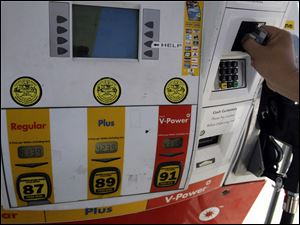 Customer Daniel Dona pays with his credit card for $4.13 a gallon at a Shell gas station in Menlo Park, Calif., in March.