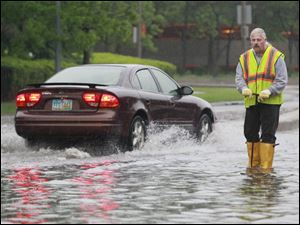 Toledo sewer worker Al Rose works on a flooded portion of the Martin Luther King, Jr., Bridge. The National Weather Service said 1.73 inches of rain fell on the Toledo area Wednesday.