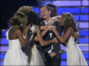 "Scotty McCreery is embraced by other ""American Idol"" contestants after winning at the finale Wednesday in Los Angeles."