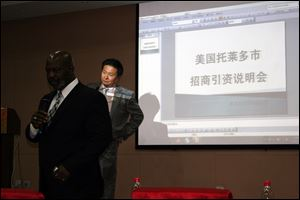 Mayor Mike Bell tells a room of Chinese investors about the merits of Toledo as Simon Guo translates. The screen behind the two men reads: 'City of Toledo Investment Demonstration.'