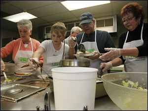 Ann Hoge, left, Crystal Bowersox, Anthony Thiros, and Lynn Carter serve lunch at St. Paul's Community Center in Toledo.