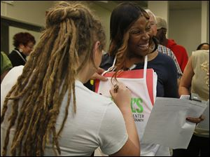 Crystal Bowersox signs an autograph for St. Paul's Community Center employee Exquatteeshia Jackson of Toledo.