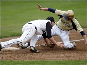 Jesse Adams, of St. John's, avoids a tag attempt by Perrysburg's Matt Garbig to steal third base.