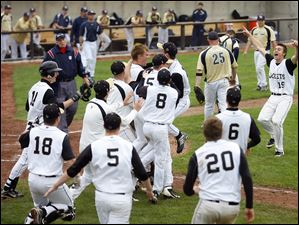 Perrysburg High School's mob teammate Steve Slocum (center without a hat) after he scores the winning run in the bottom of the 12th inning of the Yellow Jackets Division I baseball regional semifinal against St. John's at BGSU's Stellar Field.