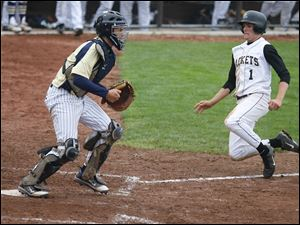 St. John's catcher Corey Tipton awaits a throw to the plate as Perrysburg's Steve Slocum scores the winning room in the 12th inning.