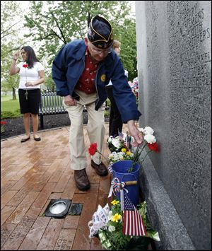 Korean War veteran Joe Stockner of Perrysburg places a flower by a World War II memorial at Waite High School after its program.
