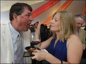 Mark Laimbeer gets a bite of food from wife Laura at Taste of the Nation.