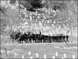 A caisson carries the casket of Army Cpl. Frank Buckles, the last American veteran of World War I, to the graveside service at Arlington National Cemetery in Arlington, Va., in this black and white image.