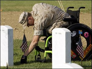 Marine Lance Cpl. Brandon Long, who was injured serving in Afghanistan, visits a friend's grave at Arlington National Cemetery.