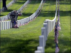 A soldier places American flags if front of each headstone at Arlington National Cemetery.