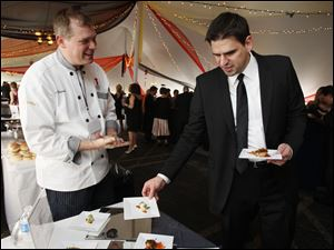 Toledo Club Chef Mike Rosendaul greets Greg Helyer as he takes some food at Taste of the Nation.