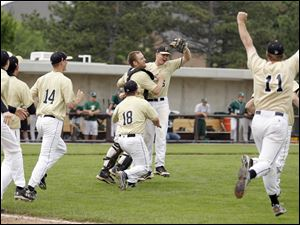 Perrysburg players celebrate after relief pitcher Alex Williams makes the final out against Strongsville to win their Division I regional baseball final.