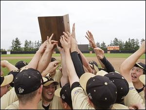 Perrysburg baseball team celebrates with its trophy after defeating Strongsville in a Division I regional baseball final at BGSU's Steller Field.