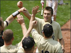 Perrysburg's Hunter Smith is greeted by teammates after scoring a run against Strongsville.