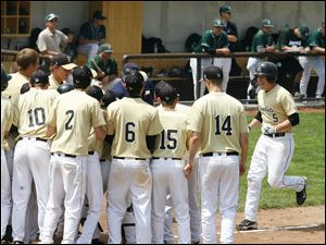 Perrysburg's Matt Garbig (5) is greeted at the plate by teammates after hitting a home run against Strongsville.